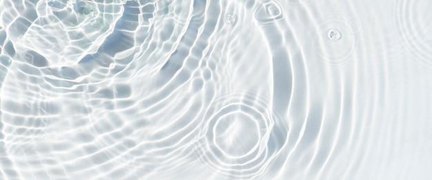 Waterdruppels vallen op het transparante oppervlak van het water in zonlicht. bovenaanzicht, plat gelegd. banier.