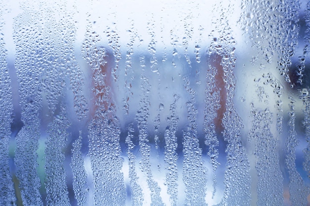 Waterdruppels van huis condensatie op een raam