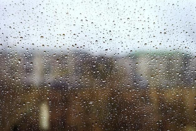 Waterdruppels van regen op het vensterglas tegen het stedelijke landschap, gekleurd