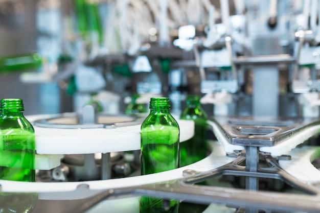 Waterfabriek - waterbottellijn voor het verwerken en bottelen van zuiver mineraalwater in kleine groene glazen flessen. selectieve aandacht.