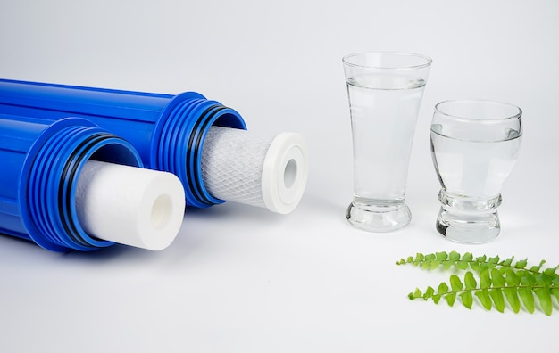 Waterfilters koolpatronen en een glas water op witte achtergrond