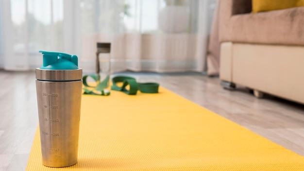 Waterfles en elastische band om thuis te trainen