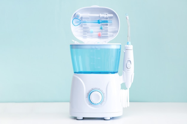 Waterflosser, tandheelkundige monddouche op een blauwe achtergrond. verzorging van tandheelkundige apparatuur. irrigator voor mond