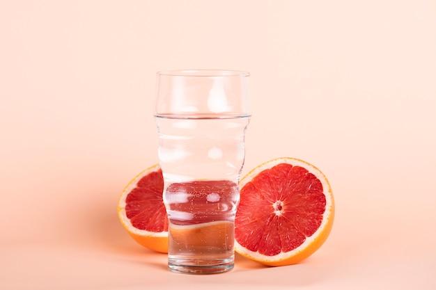 Waterglas en roodoranje arrangement