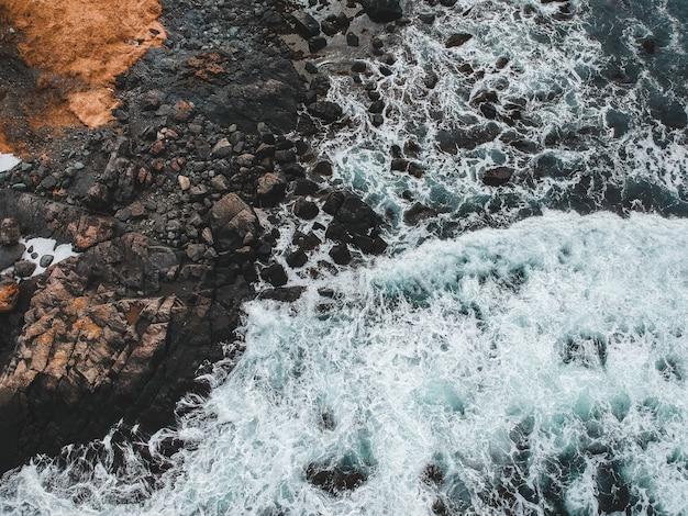 Watergolven die bruine rotsen raken