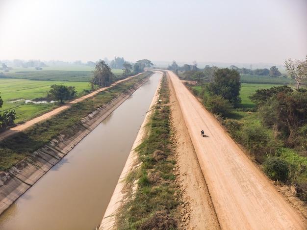 Waterkanaal naast padieveld in aziatisch land
