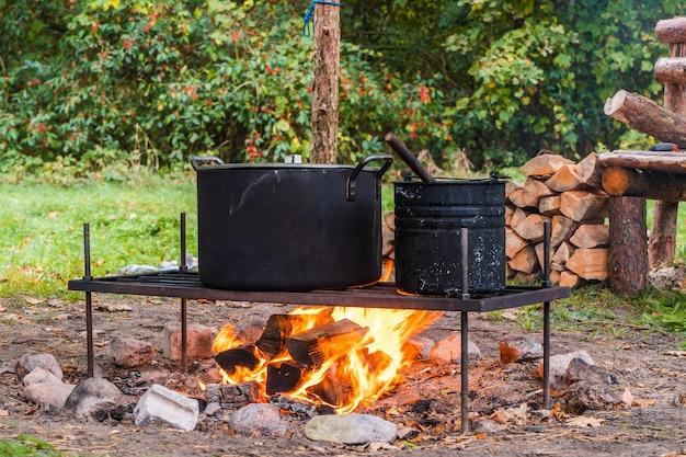 Waterkoker boven kampvuur. eten in het wild koken. kamperen, reizen en toerisme concept