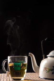 Waterkoker en kopje thee, beide komen uit rook op een houten mat