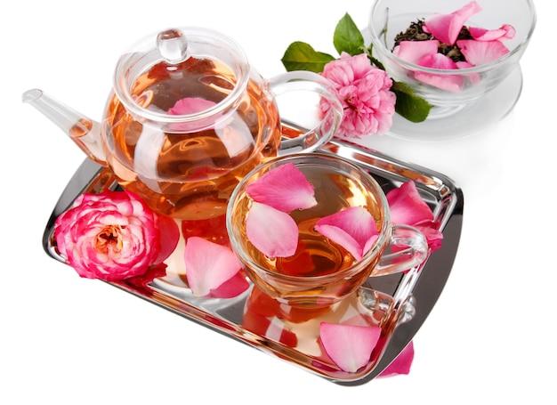 Waterkoker en kopje thee uit thee roos op metalen dienblad op wit