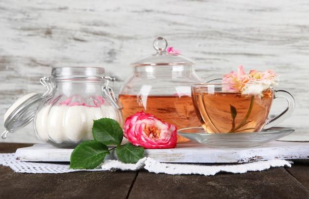 Waterkoker en kopje thee van thee roos aan boord op servet op houten tafel op houten achtergrond