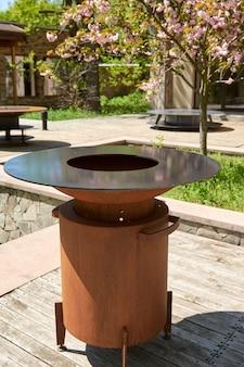 Waterkoker grill pit met gietijzeren rooster met vlammen ronde tafel kookoppervlak hete bbq op achtertuin