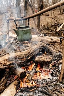 Waterkoker hangend boven een vuur in het bos, bij een picknick