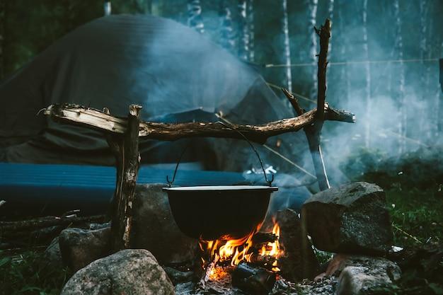 Waterkoker in brand dichtbij tent in bos bij nacht. mooi kampvuur in toeristenkamp in wildernis. overleven in taiga. ketel boven vreugdevuur. rook van vuur tussen bomen. koken boven kampvuur.