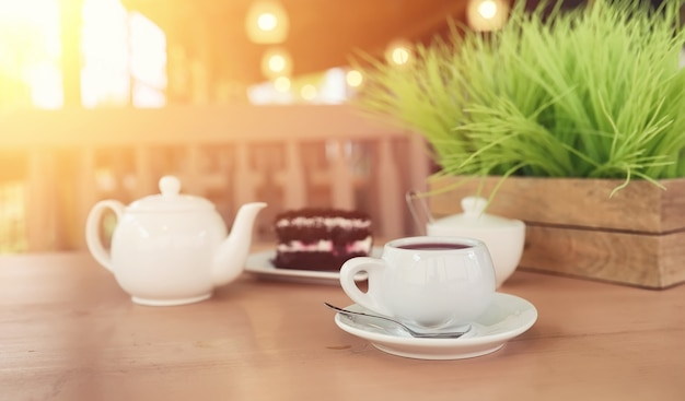 Waterkoker met een drankje en dessert in straatcafé. thee in de waterkoker beker op tafel. ontbijt met thee en gebak in het café.
