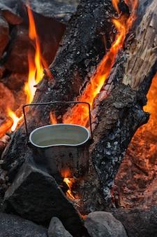 Waterkoker op houtskool, brandende houtblokken