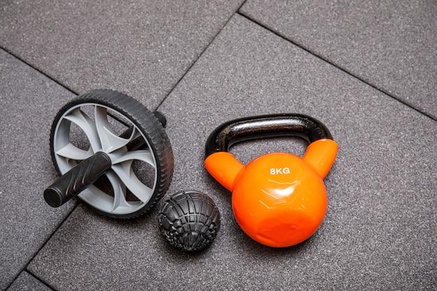 Waterkokerklokken, medicijnbal en halters op de zwarte sportschoolvloer, fitnessapparatuur. sportoefening ontwerp. plat lag met copyspace voor tekst.