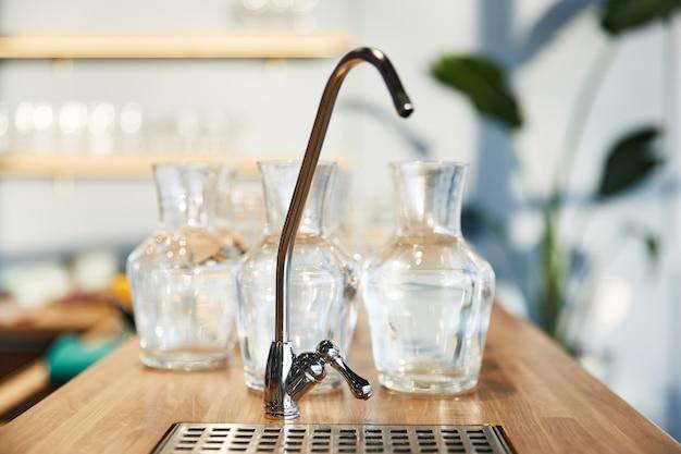 Waterkraan van vele glas grote vazen die zich op houten countertop bevinden