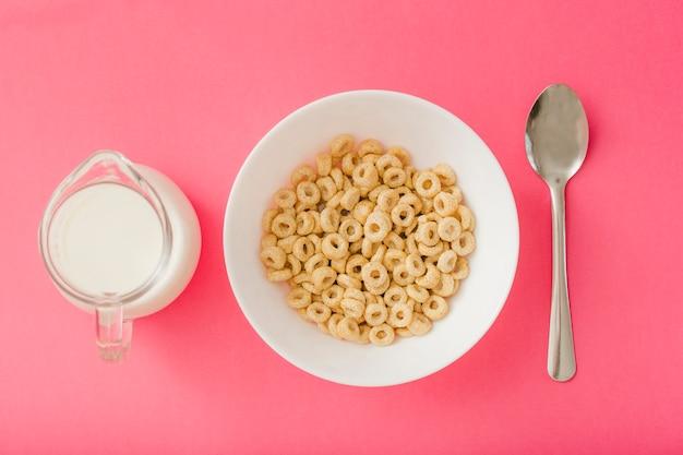 Waterkruik melk en kom graangewassen en lepel op de rode achtergrond