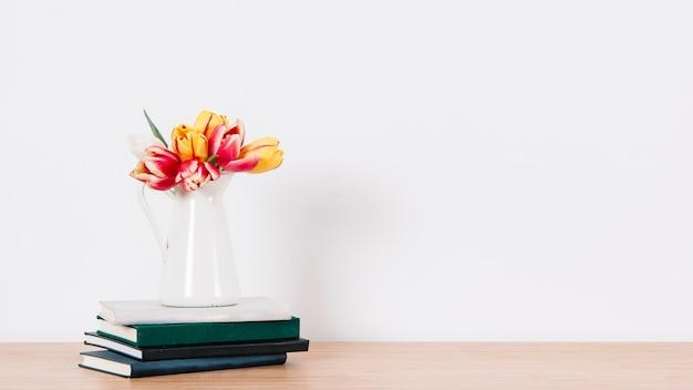 Waterkruik met tulpen op blocnotes