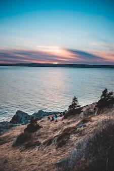 Watermassa dichtbij bruine rotsvorming tijdens zonsondergang