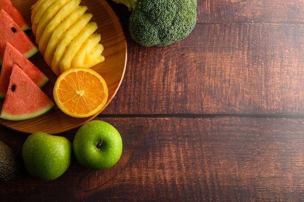 Watermeloen, ananas, sinaasappelen, in stukken gesneden met avocado, broccoli en appels op houten tafel. bovenaanzicht.