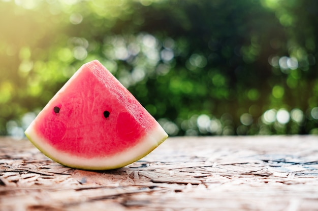 Watermeloen die op houten lijst wordt gesneden.