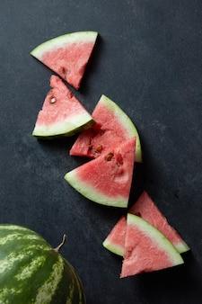 Watermeloen en plakjes op een zwarte tafel