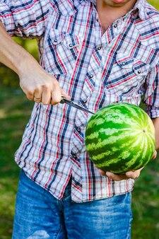Watermeloen in de handen van een man op de natuur in het park