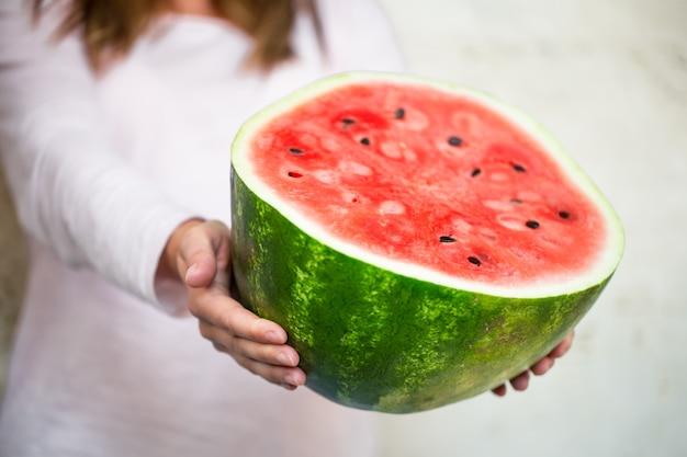 Watermeloen in de handen van het meisje close-up