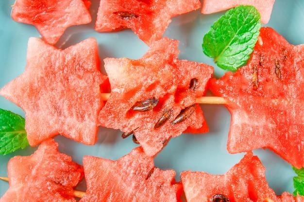 Watermeloen in de vorm van sterren op spiesjes met bladeren van mint ligt op een blauwe plaat.