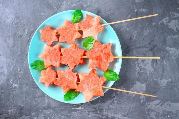 Watermeloen in de vorm van sterren op spiesjes met bladeren van mint ligt op een plaat.