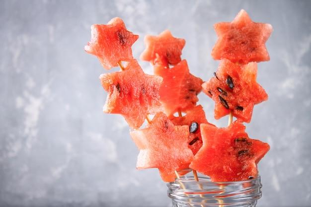 Watermeloen in de vorm van sterren op spiesjes met muntblaadjes zit in een glazen pot.