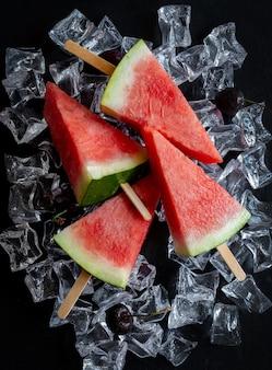 Watermeloen in een vorm van ijslollyijs op ijsblokjes gesneden
