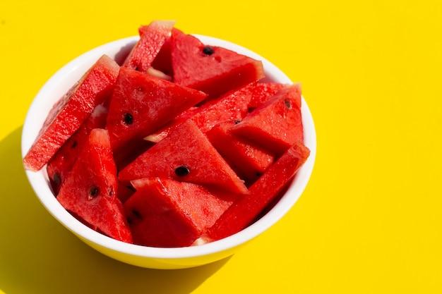Watermeloen in witte kom op gele achtergrond.