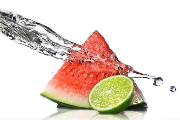 Watermeloen, limoen en water splash geïsoleerd op wit
