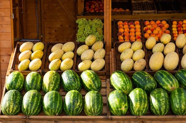 Watermeloen, meloen, perzik, druiven te zien op de markt.
