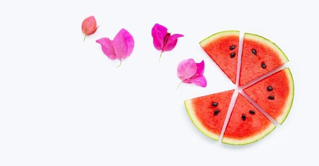 Watermeloen met bougainvillea bloem op gele achtergrond.