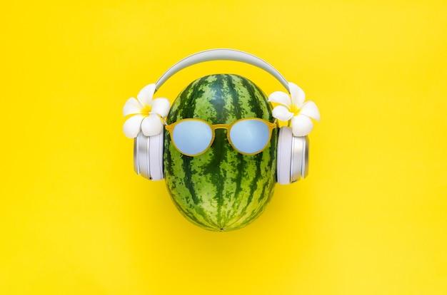 Watermeloen met draadloze hoofdtelefoon met witte frangipanibloemen op gele achtergrond
