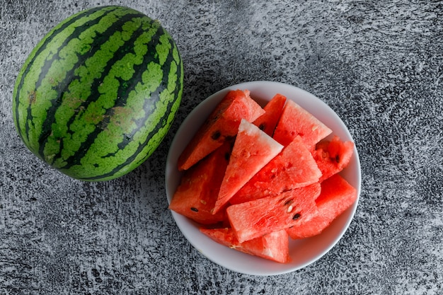Watermeloen met plakjes op grijze grunge tafel