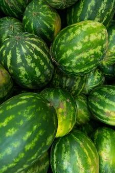 Watermeloen met streeppatroon voor achtergrond bij de markt van de landbouwer of kruidenierswinkelopslag, verticale foto