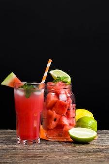 Watermeloen natuurlijk sap en stukjes rode sappige watermeloen gesneden op de tafel, natuurlijk voedingsproduct