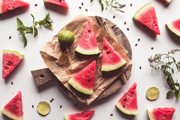 Watermeloen op een gesneden bord met munt en schijfjes limoen. voedsel