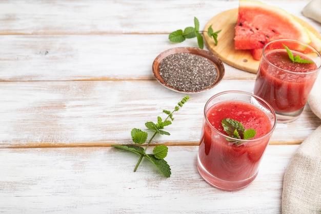 Watermeloen sap met chiazaadjes en munt in glas op een witte houten achtergrond met linnen textiel. gezond drankje concept. zijaanzicht, kopieer ruimte.