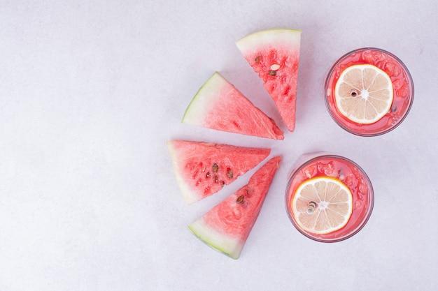 Watermeloen sap met plakjes rood fruit op wit.