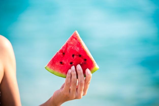 Watermeloen slice in vrouw overhandigen zee
