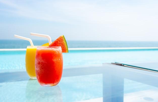 Watermeloen smoothie en mango smoothie met zwembad en zee strand
