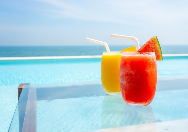 Watermeloen smoothie en mango smoothie met zwembad en zee