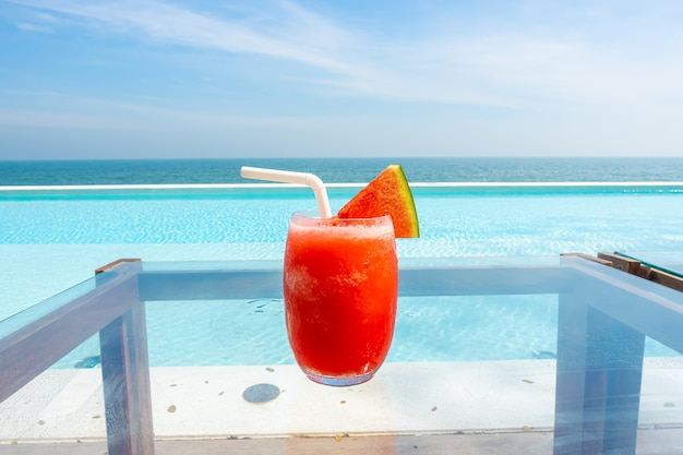 Watermeloen smoothie met zwembad en zee strand