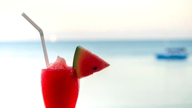 Watermeloen smoothies portie in glas op strand in de zomer