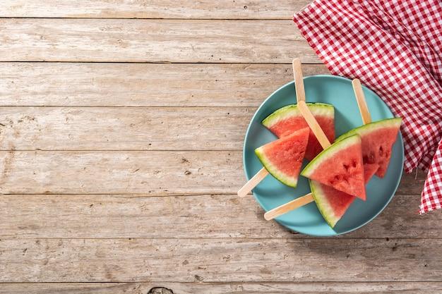 Watermeloen snijdt ijslolly's op blauwe plaat en houten tafel